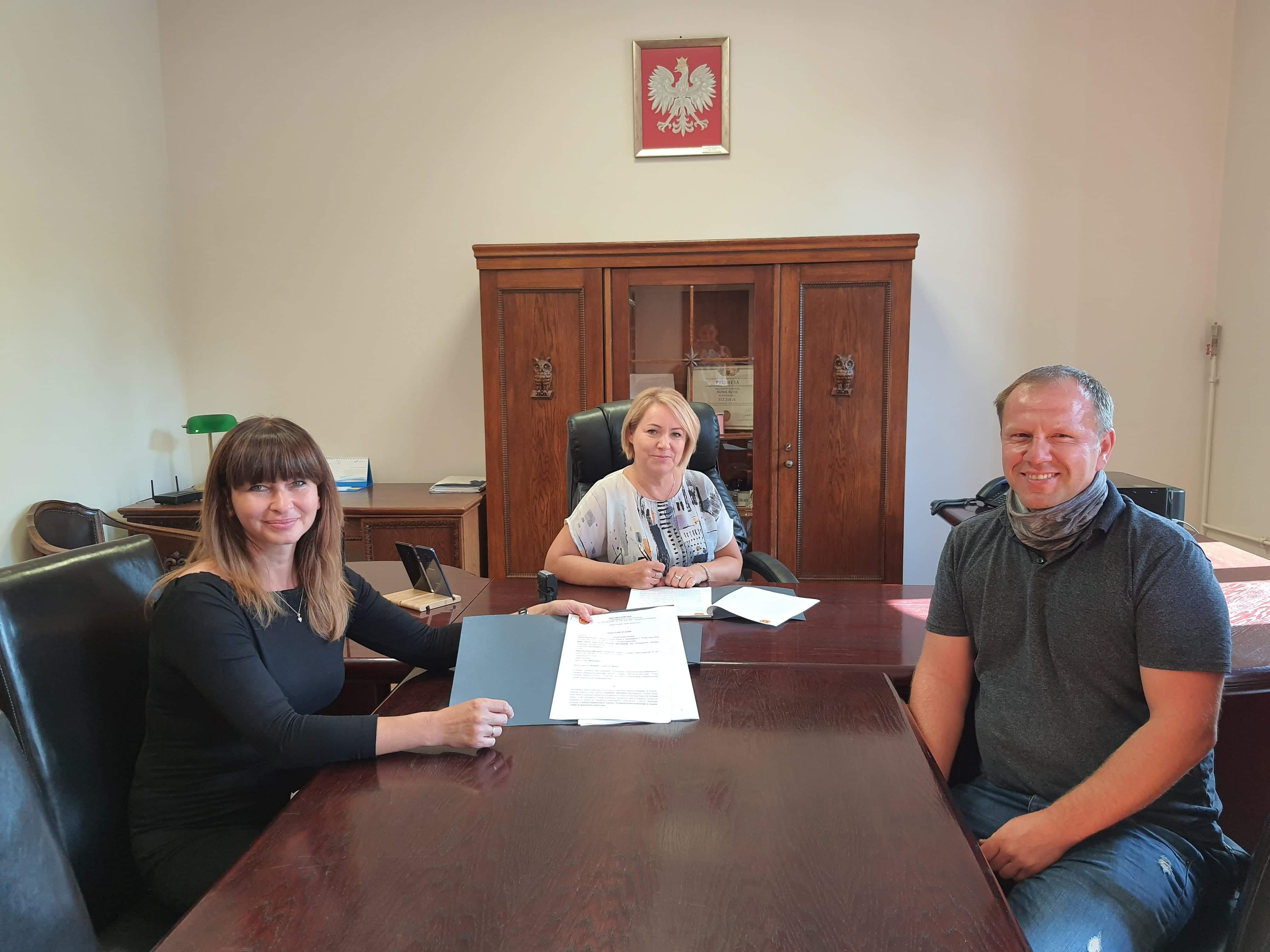 Na obrazku widoczne są trzy osoby, Wójt Gminy Adrianna Mierzejewska, Izabela Słowek-Chorób oraz przedstawiciel firmy SMILEBUS, zdjęcie przedstawia podpisanie umowy.